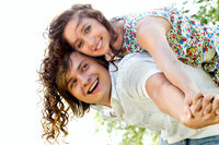 Young man giving piggyback to happy woman