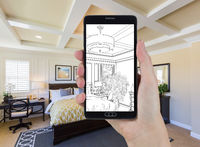 Hand Holding Smart Phone Displaying Drawing of Bedroom Photo Behind