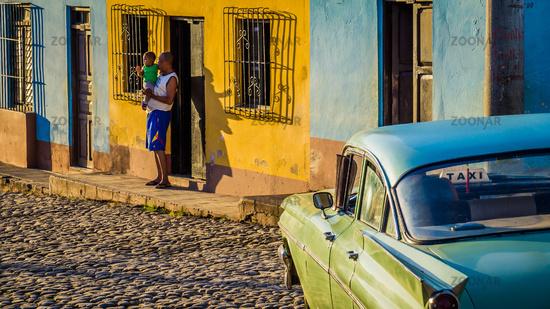Cubans with oldtimer taxi in Trinidad