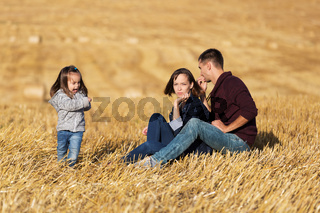 Happy young family with two year old girl sitting on the ground in harvested field