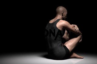 Sad, depressed man sitting alone on floor in dark spotlight. Depression, pain