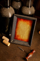 Dusty wine bottles, corkscrew and picture frame