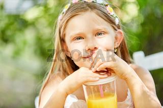 Mädchen trinkt Orangensaft mit dem Strohhalm