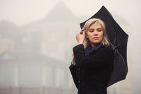 Young fashion woman with umbrella walking in a fog outdoor