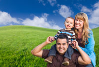 Mixed Race Family In Green Grass Field