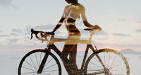 Double exposure of a naked woman with bicycle combined with sunset above the sea