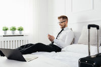 Young businessman working from a hotel room with his mobile phone