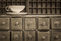 classic tea cup on top of rustic drawers