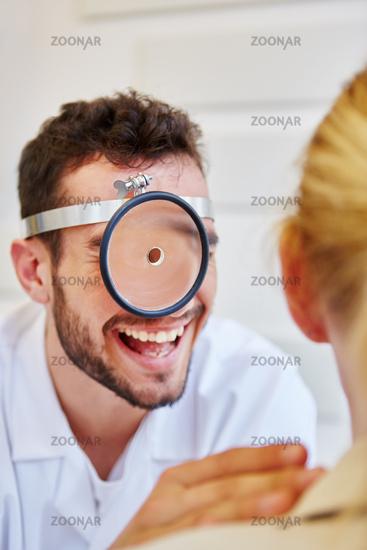 HNO-Arzt mit Stirnspiegel lacht