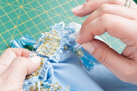 woman sews a decorative element to clothes with a needle