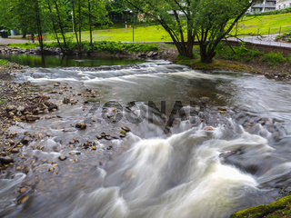 Strong current in river passing around rocks with long exposure