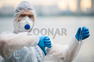 Biologist in respirator with test-tube