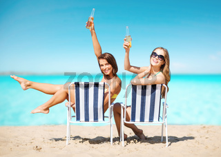 happy young women with drinks sunbathing on beach