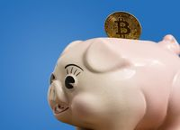 Single bitcoin coin being placed in piggy bank