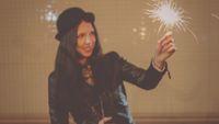 Defocused image of happy girl in hat with burning sparkler in her hands, vintage looking toned shot, instagram color