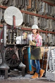 Junge Frau im Material Lager einer Metallfabrik