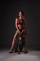 Erotica. Domineering mistress posing with doberman