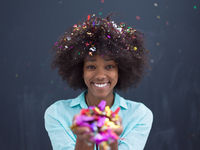 black woman blowing confetti in the air
