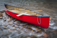 red canoe on a shallow rocky river