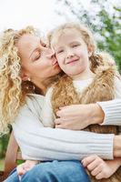 Mutter küsst und umarmt Tochter