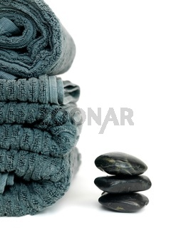 An aroma therapy image with river rocks and bath towels isolated against a white background