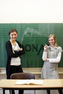 Lehrerin und Schülerin vor der Tafel -