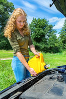 Young caucasian woman fills car motor with oil