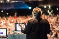 Female public speaker giving talk at Business Event.