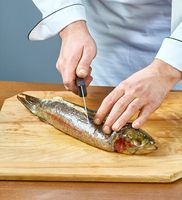 The cook cuts the baked fish a full collection of food recipes