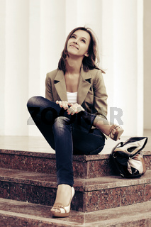 Happy young fashion woman with handbag sitting on the steps