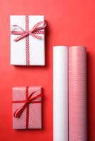 Two Wrapped Christmas presents with matching paper rolls and copy space.