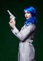 Portrait of young woman in comic  pop art make-up style.  Female with gun in hand