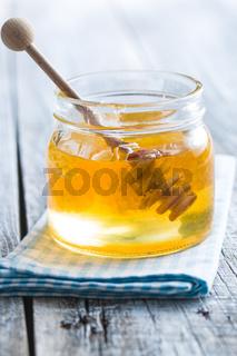 Wooden honey stick in jar.