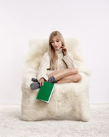 Blonde woman on furry arm-chair with book in hands