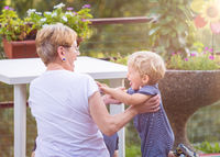 Grandmother and grandchild happily play in the garden. Natural light.