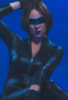 Brunette girl dressed in leather and latex fitted with pistol on blue background