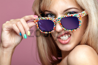 Young blonde woman with fun candy glasses on pink background