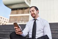 Junger Geschäftsmann liest eine SMS