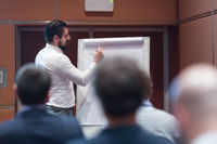 Skiled Businessman Presenting a Project to His Work Team at Informal Company Meeting.