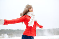 happy woman in winter fur hat outdoors