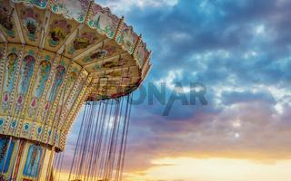 Wave Swinger corousel ride against blue sky, vintage filter effects