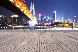 empty wooden floor with modern bridge and modern city