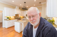 Happy Senior Man In Custom Kitchen Interior