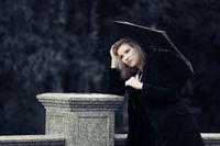 Sad young fashion woman with umbrella in the rain
