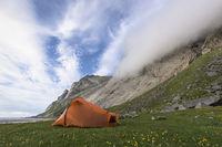 Tent beside a cliff wall, Buneset, Moskenesoeya, Lofoten, Norway