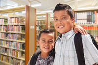 Young Hispanic Student Brothers In Library