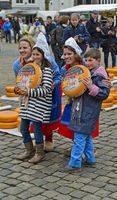 Dutch cheese girls and two kids pose with Gouda cheese truckles for a souvenir photo, cheese market