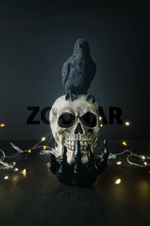 Creepy skull with black bird sitting on skeleton hand