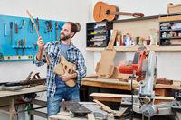 Gitarrenbauer hält Korpus und Griffbrett