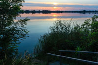 Wooden stairs to summer sunset lake